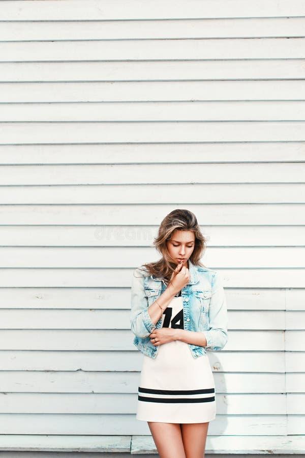 Recht trauriges einsames Mädchen nahe einer weißen hölzernen Wand stockbilder