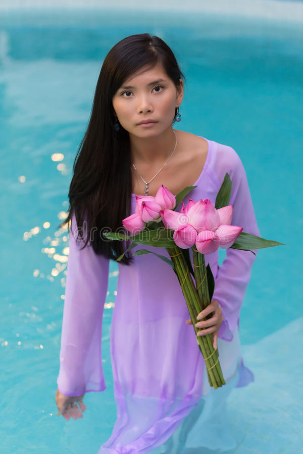 Recht vietnamesische Frau, die im Wasser steht stockfotografie