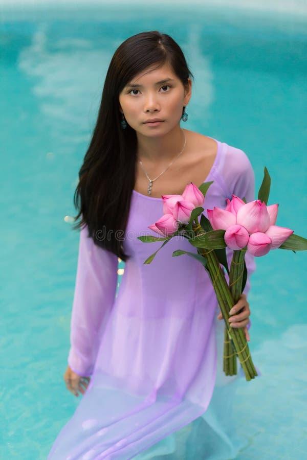 Recht vietnamesische Frau, die im Wasser steht stockfotos