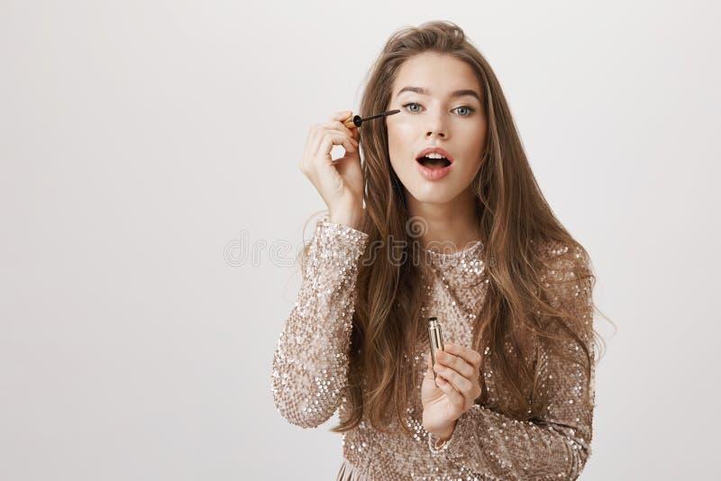 Recht weibliche europäische Frau, die auf Wimperntusche mit geöffnetem Mund, tragendes funkelndes modisches Abendkleid, betrachte lizenzfreie stockfotografie