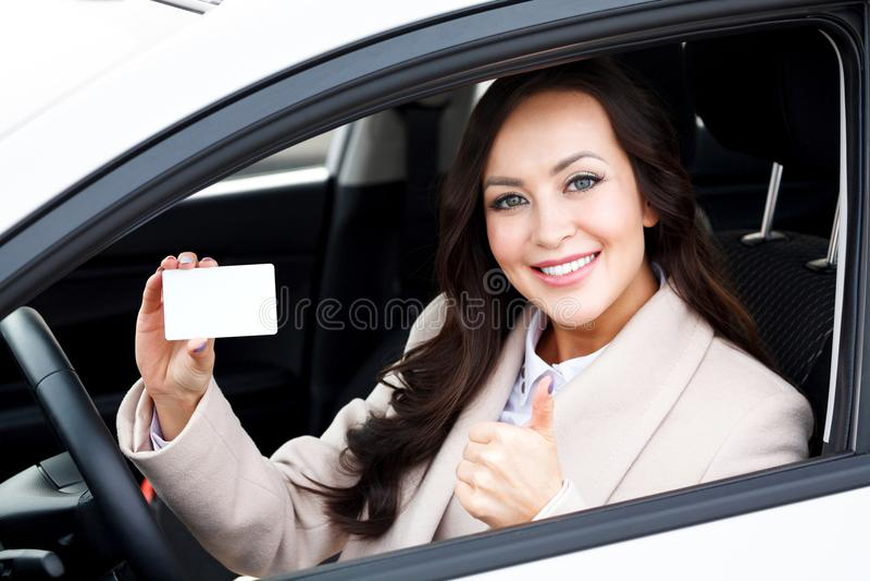 Recht weiblicher Fahrer, der leere weiße Karte zeigt lizenzfreies stockfoto