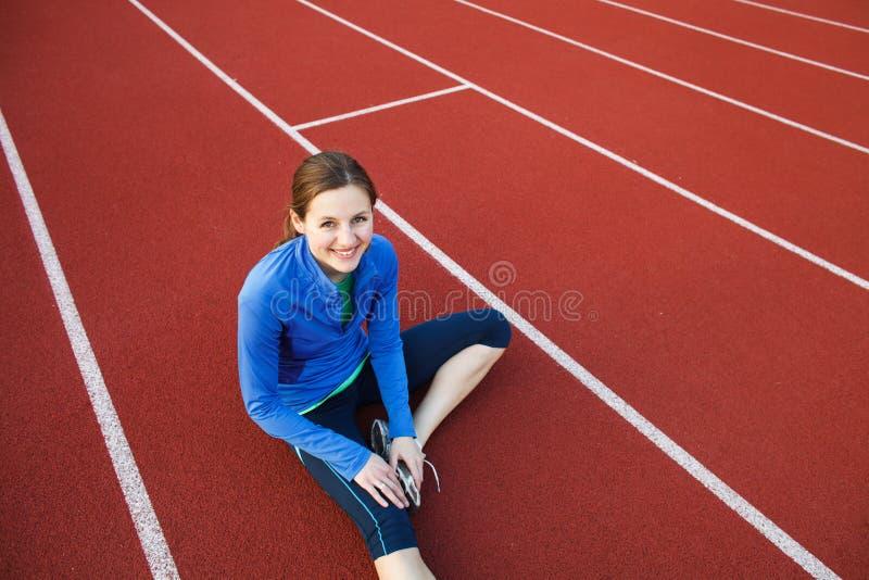 Recht weiblicher Läufer, der vor ihrem Lauf ausdehnt lizenzfreies stockfoto