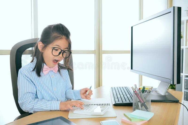 Recht wenig Büroangestelltmädchen, das Taschenrechner verwendet stockfotos