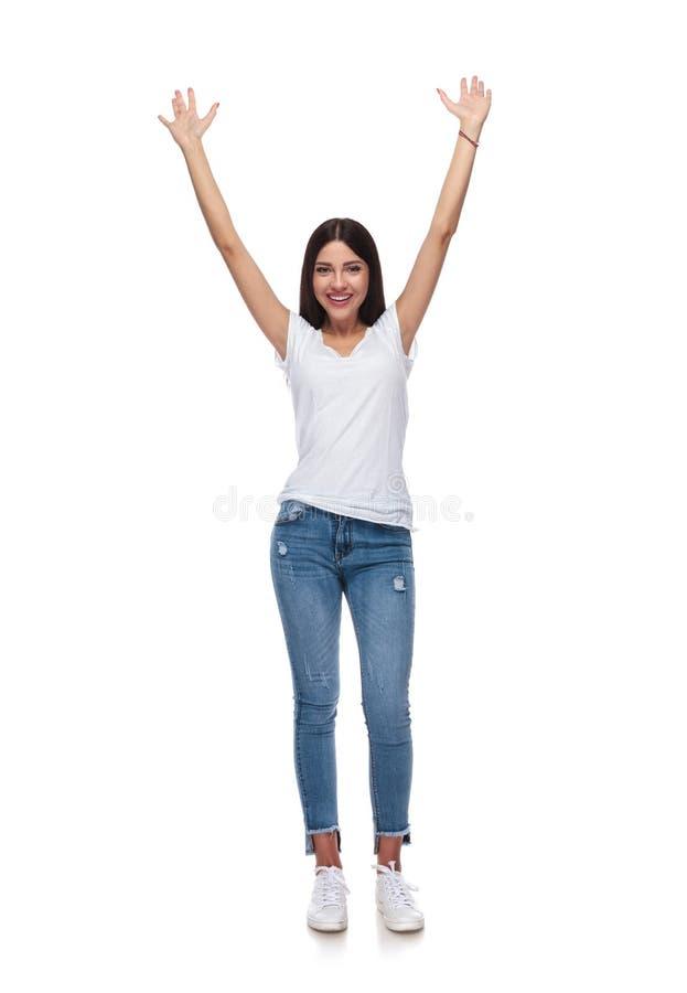 Recht zufällige Frau, die mit den Händen in der Luft feiert stockbilder