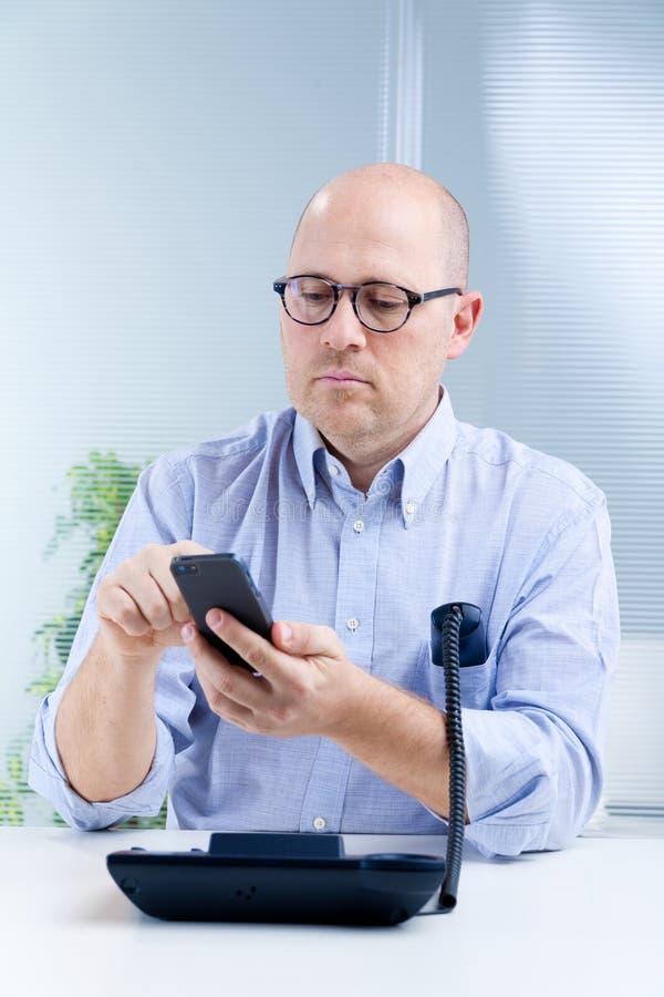 Rechte nerdy bediende met twee telefoons stock foto's