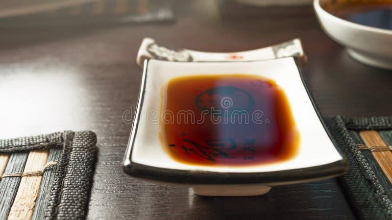 Rechteckige Sojasoße, die Teller auf einer dunklen Tabelle mit speisenden Bambusmatten eintaucht Essstäbchenhalter, Schüssel in u stockfoto