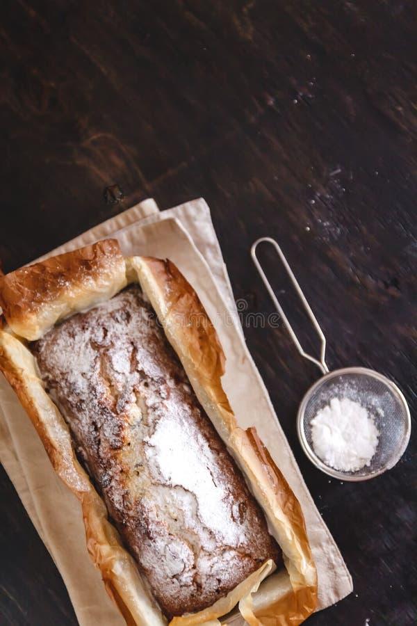 Rechteckiger Hauptkleiner kuchen mit Puderzucker in einer Metallbackform auf einem dunklen Hintergrund Nahaufnahme Ansicht von ob lizenzfreies stockbild