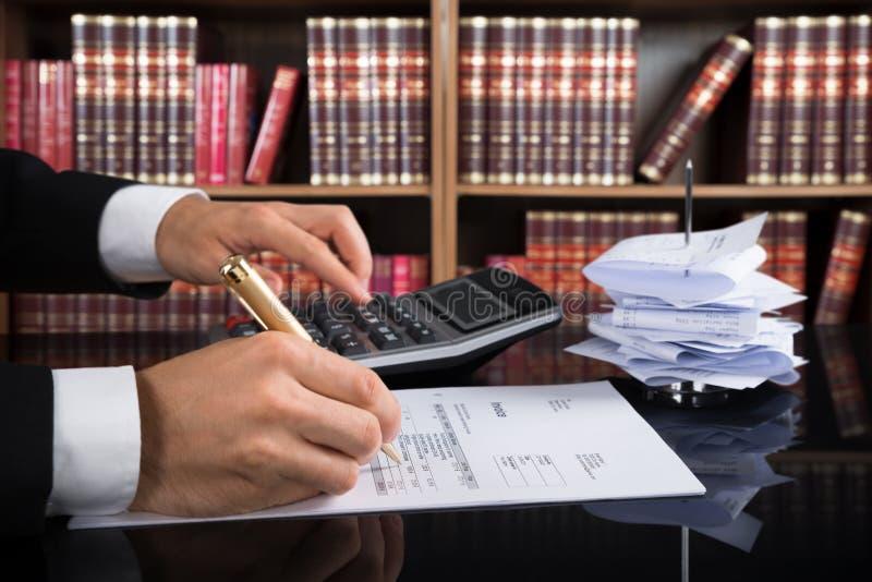 Rechter Calculating Invoice In een Rechtszaal stock foto's