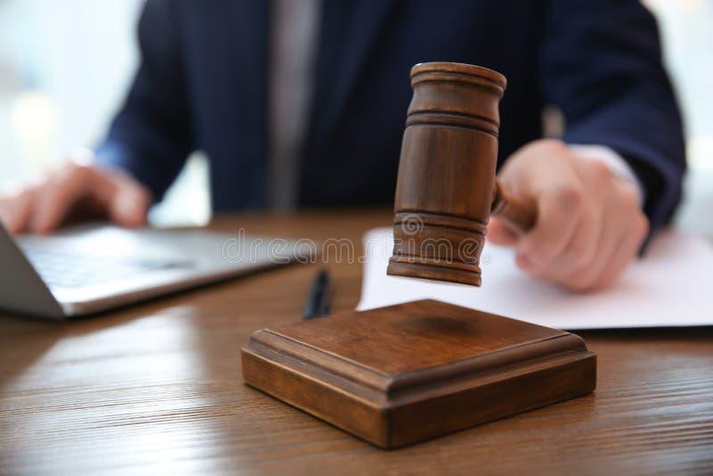 Rechter met hamer bij lijst in rechtszaal Wet en rechtvaardigheidsconcept stock foto's