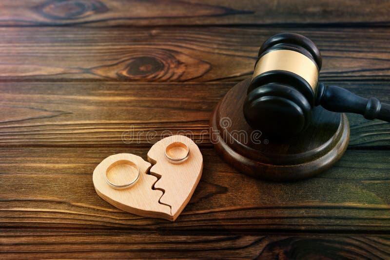 Rechters` s hamer, een gebroken hart van hout, een paar gouden trouwringen tegen royalty-vrije stock afbeelding