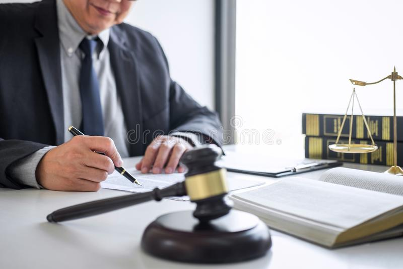 Rechtershamer met Rechtvaardigheidsadvocaten, Adviseur in kostuum of advocaat die aan documenten in rechtszaal werken, Wettelijke stock foto