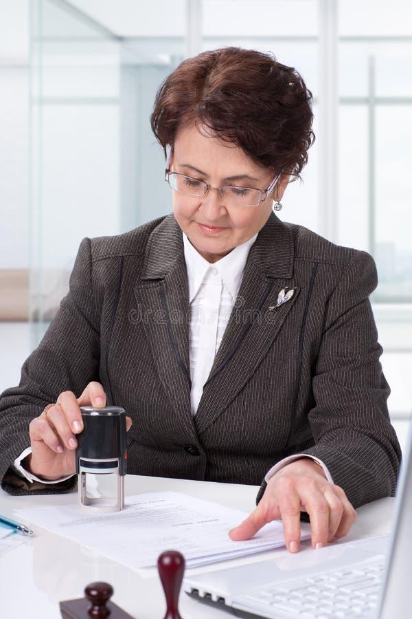 Rechtsanwalt auf seinem unterzeichnenden Vertrag des Arbeitsplatzes stockbild