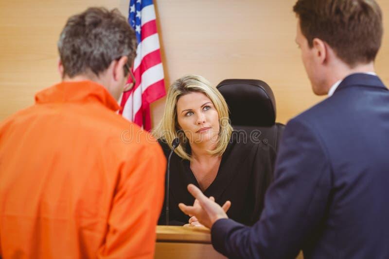Rechtsanwalt, der über den Verbrecher im orange Overall spricht lizenzfreie stockfotografie