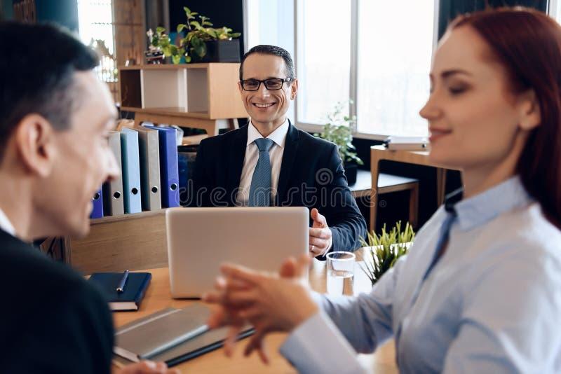 Rechtsanwalt im Anzug sitzt im Büro und hört auf Diskussion über Scheidungspaare lizenzfreie stockfotos