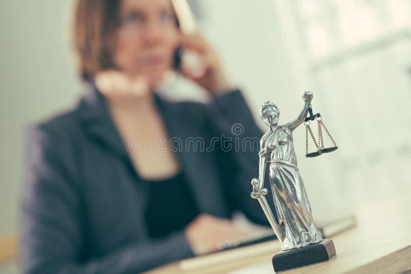 Rechtsanwaltsfrau, die am Handy von ihrem Schreibtisch spricht lizenzfreie stockbilder