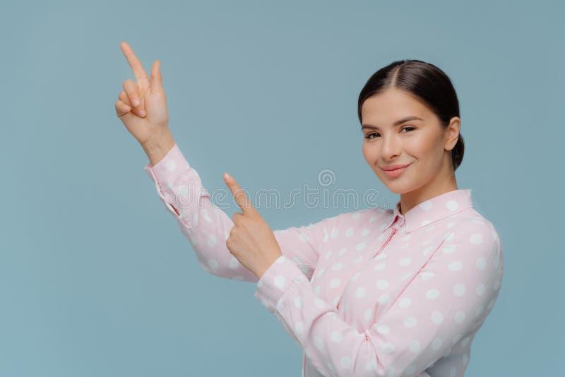 Rechtstreeks glimlachend Kaukasische vrouwelijke punten tot bovenkant, toont iets bij hogere linkerhoek aan, heeft tevredengestel stock fotografie