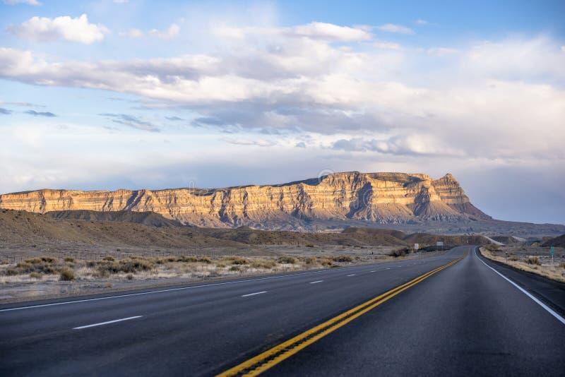 Rechtstreeks verdeelde lange weg die tegen de horizon in Arizona met bergheuvels en woestijnplateau grenst aan stock fotografie