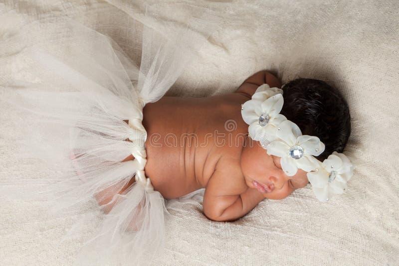 Recién nacido afroamericano el dormir con el tutú y la venda floral fotografía de archivo