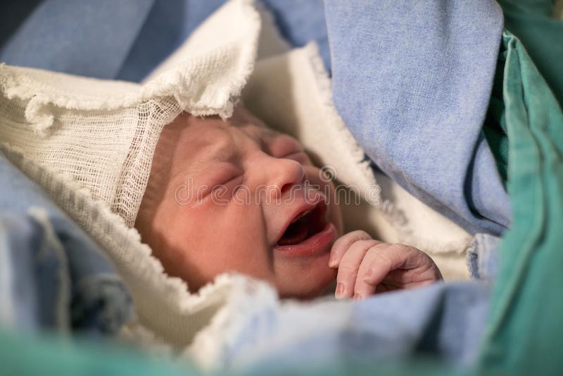 Recién nacidos, los ojos se cerraron, bebé gritador en manta verde en hospital fotografía de archivo libre de regalías