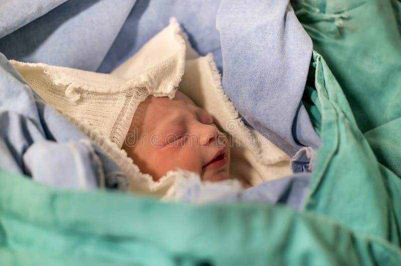 Recién nacidos, los ojos se cerraron, bebé gritador en manta verde en hospital fotografía de archivo