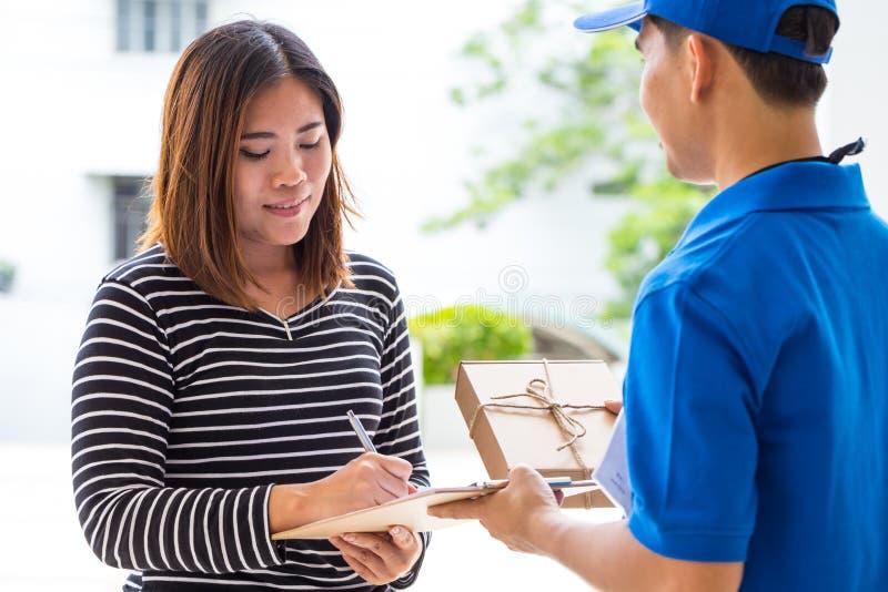 Recibo de firma de la mujer asiática del paquete entregado foto de archivo libre de regalías