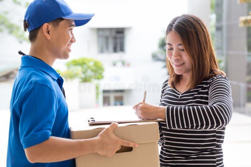 Recibo de firma de la mujer asiática del paquete entregado imagen de archivo