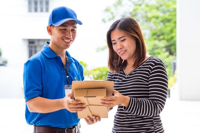 Recibo de firma de la mujer asiática del paquete entregado foto de archivo