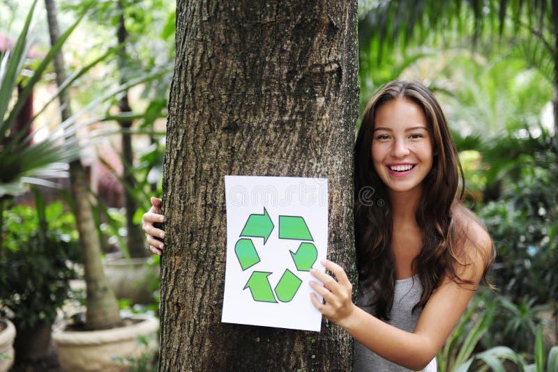 Recicl: a mulher na floresta com recicl o sinal fotografia de stock