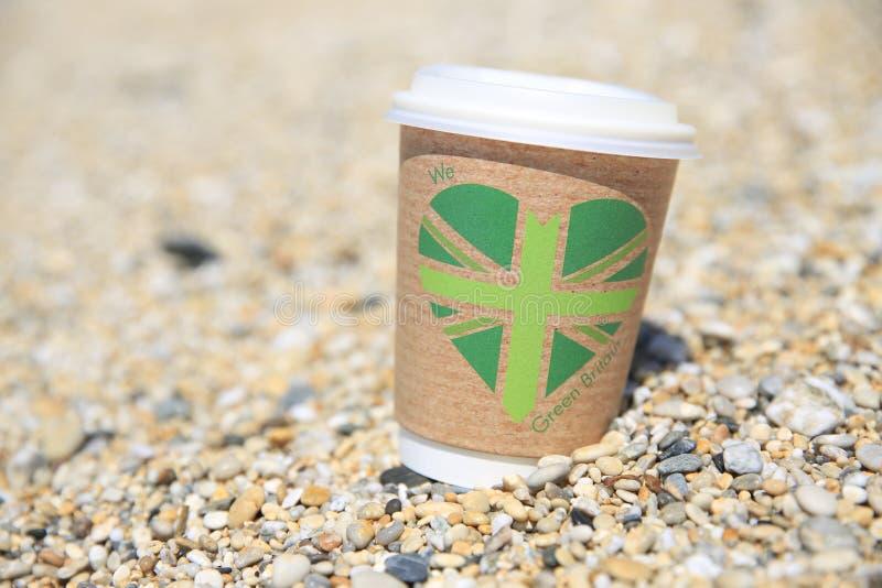 Reciclable llévese la taza de café lavada para arriba en una playa fotografía de archivo libre de regalías