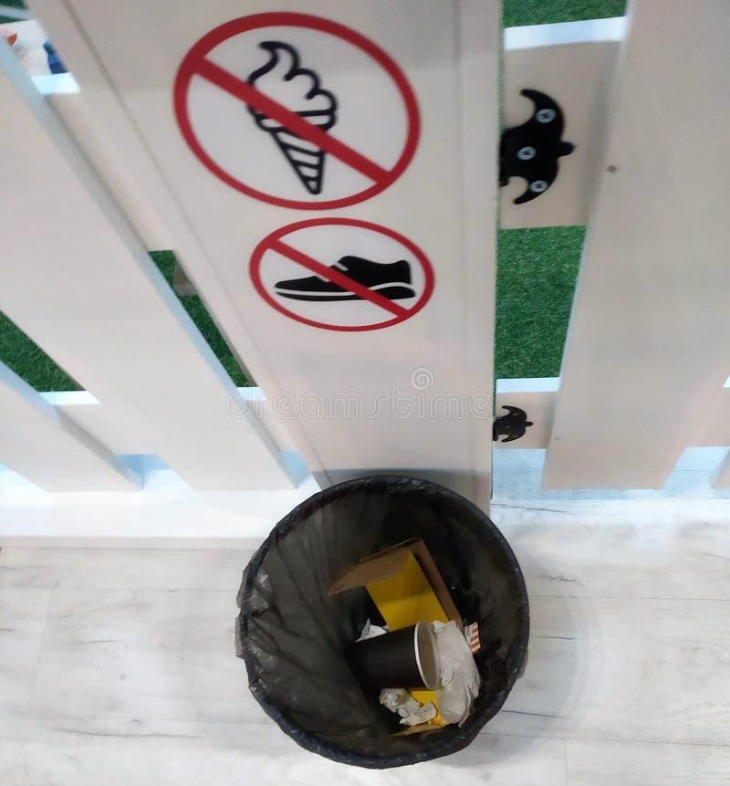 A reciclagem com lixo em um pacote plástico da cor preta, uma fileira tirou sinais da proibição em um fundo branco, imagem de stock