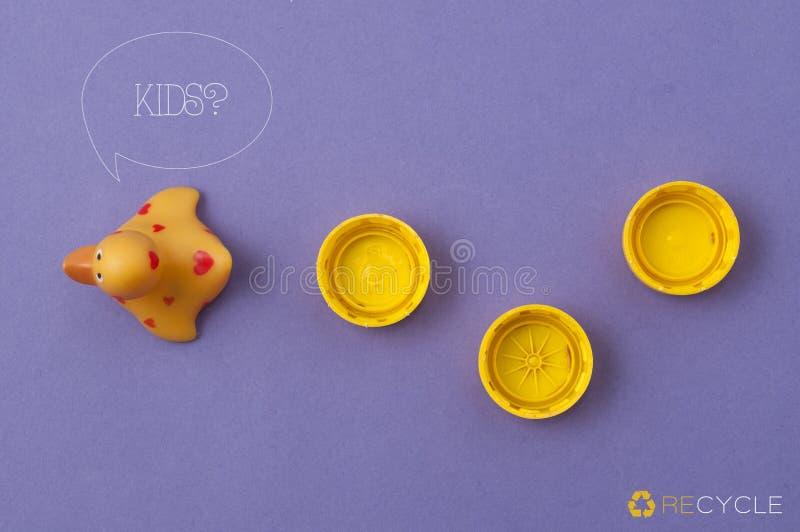 Reciclaje de concepto: un pato plástico amarillo seguido por tres casquillos amarillos plásticos imagen de archivo