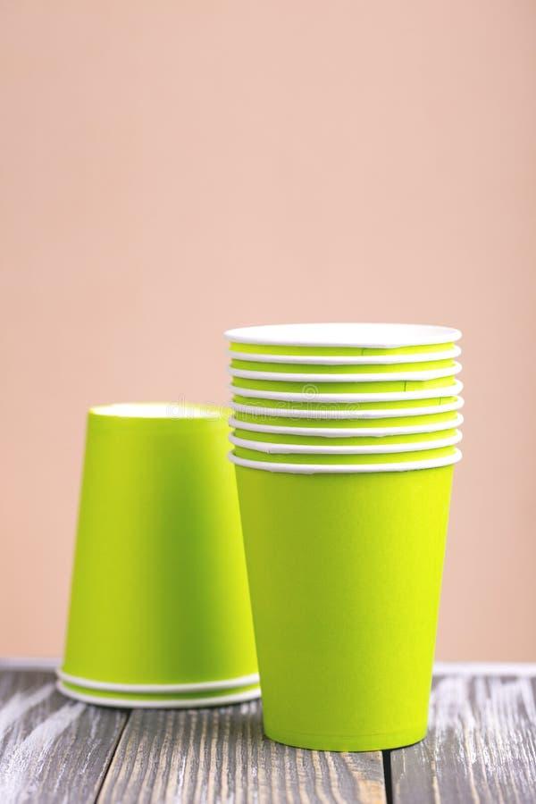 Reciclaje de las tazas de papel brillantes y coloridas en la tabla de madera Visión horizontal imagen de archivo libre de regalías