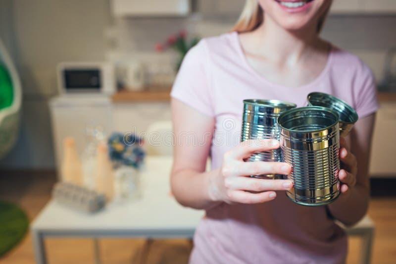 reciclaje Las latas del metal se preparan para reciclar La mujer responsable está protegiendo el ambiente mientras que clasifica imagenes de archivo
