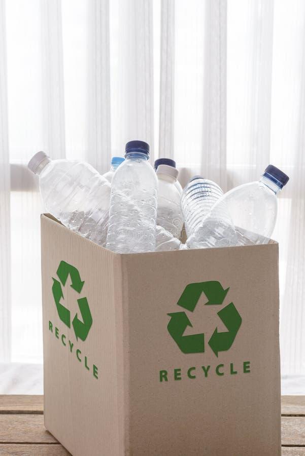 Reciclando la caja llenada de los envases del plástico transparente foto de archivo