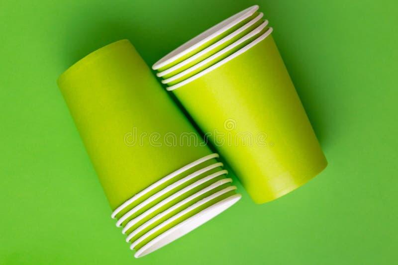 Reciclando os copos de papel para bebidas no fundo verde-claro imagens de stock