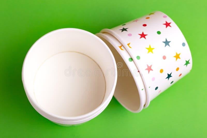 Reciclando os copos de papel para o gelado no fundo verde-claro Vista superior imagens de stock