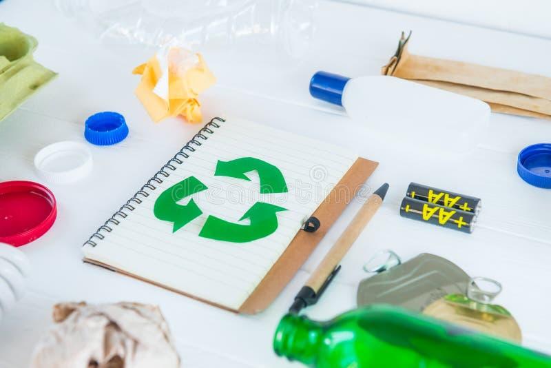 Recicle el cuaderno del papel con símbolo verde del eco rodeado con basura de la ausencia de reciclaje y basura reutilizable como imagen de archivo libre de regalías