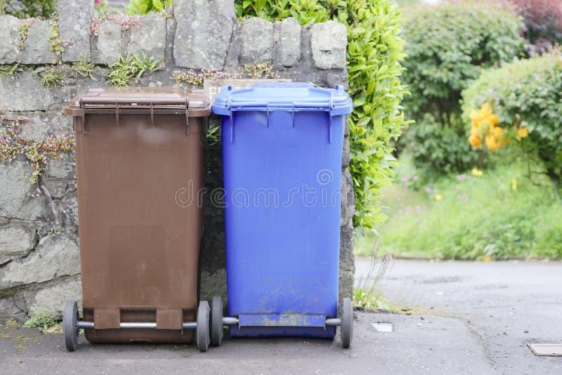 Recicle os escaninhos do wheelie marrons e azuis em Inglaterra imagem de stock royalty free