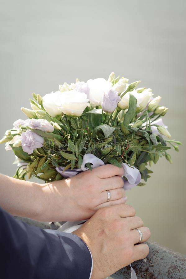 Recienes casados con un ramo de rosas blancas en sus manos en fondo neutral foto de archivo libre de regalías