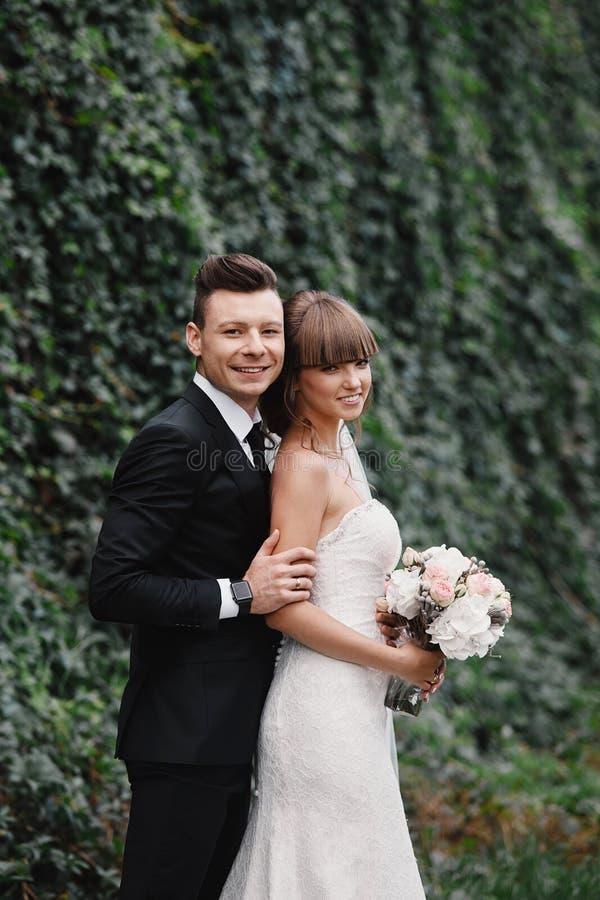 Recienes casados de los pares, soportes de novia y del novio y ramo felices el sostenerse de flores y de verdes en el jardín fotografía de archivo libre de regalías