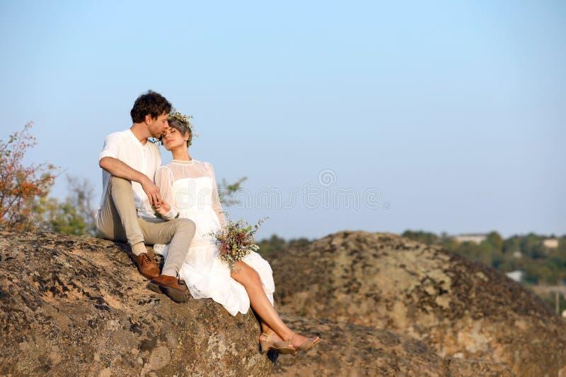 Recienes casados felices con el ramo hermoso del campo que se sienta en roca fotos de archivo libres de regalías