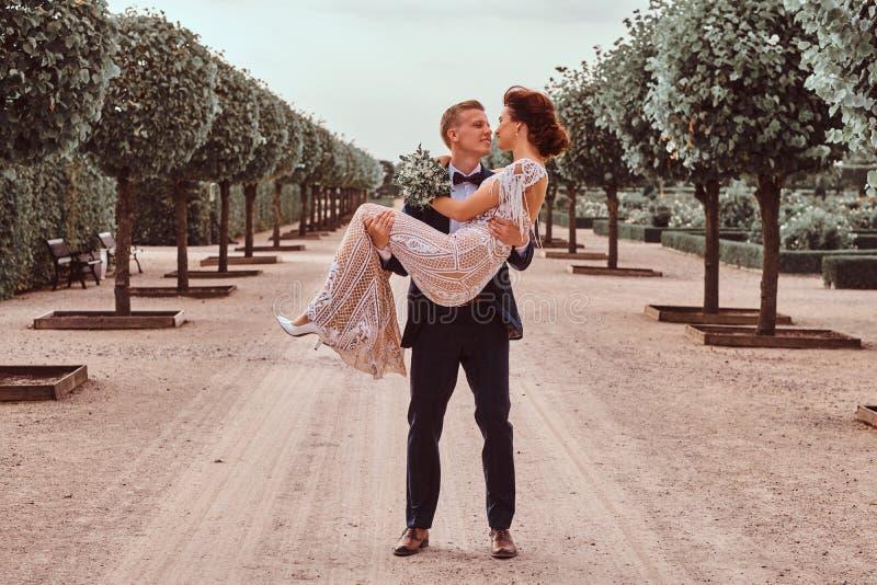 Recienes casados felices El novio hermoso detiene a su novia encantadora en sus brazos en el jardín asombroso fotos de archivo libres de regalías