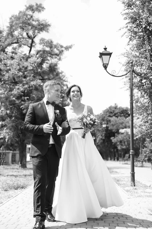 Recienes casados felices que caminan al aire libre, blanco y negro imágenes de archivo libres de regalías