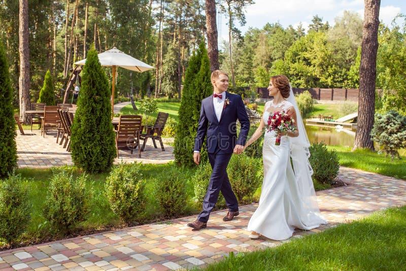 Recienes casados felices que llevan a cabo las manos y que caminan en la calzada en el verano p imágenes de archivo libres de regalías
