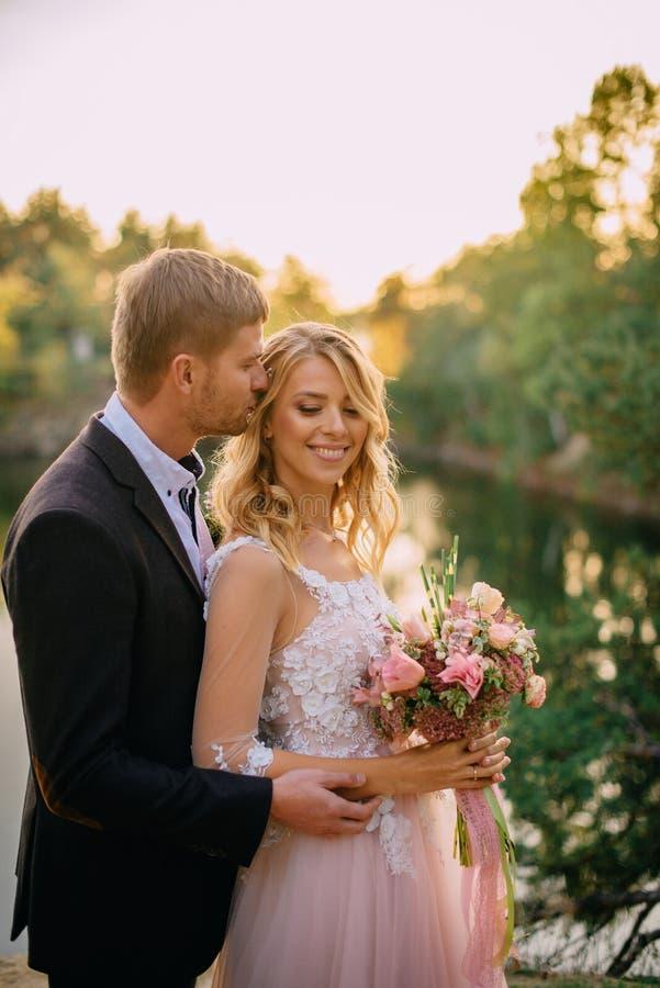 Recienes casados felices que se oponen a fondo de la naturaleza en la puesta del sol imagenes de archivo