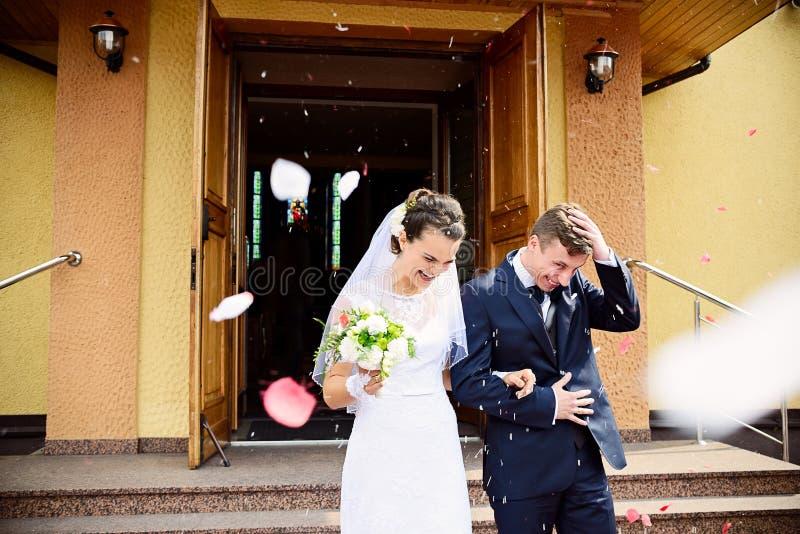 Recienes casados que salen de la iglesia después de ceremonia de boda imagenes de archivo