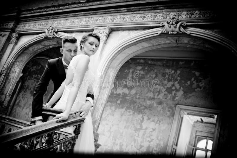 Recienes casados que se besan cerca de las escaleras viejas imagen de archivo