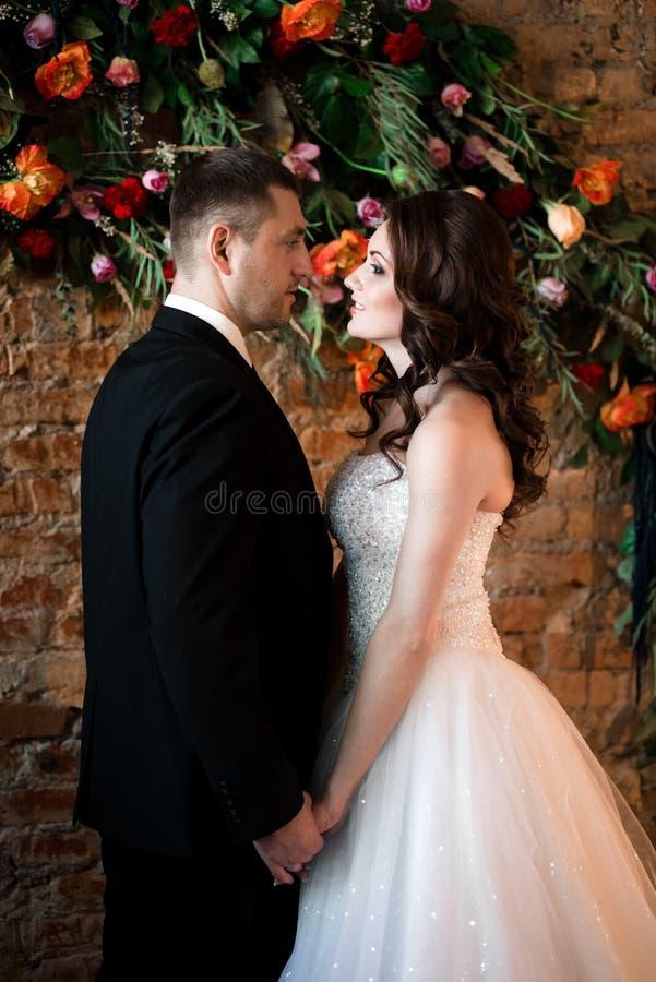 Recienes casados que se colocan de cerca de mirada feliz fotografía de archivo libre de regalías