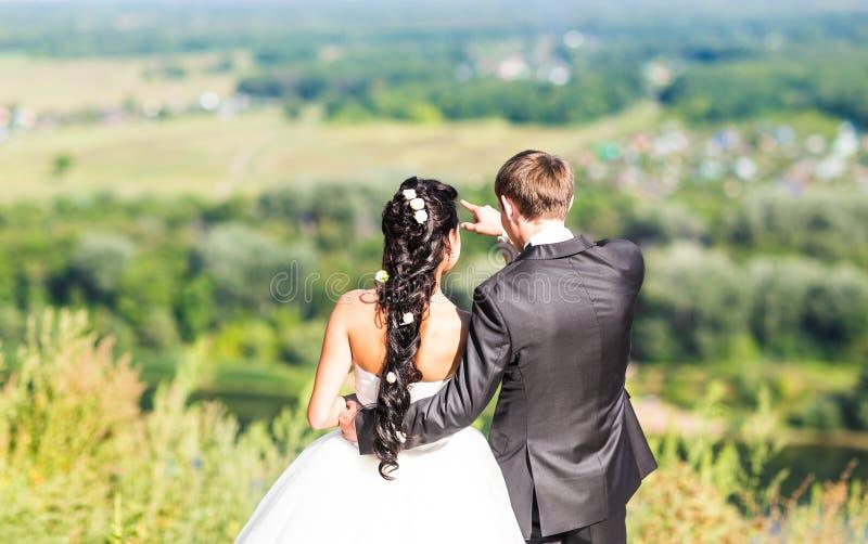 Recienes casados sonrientes felices que tienen la diversión y besarse foto de archivo