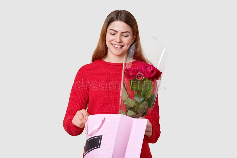 Recieving present is my favourite thing. Smiling pleased young lady opens package, sees something appealing, holds red roses, stock images